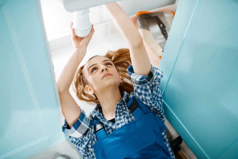 Female plumber lying on the floor, top view royalty free stock images