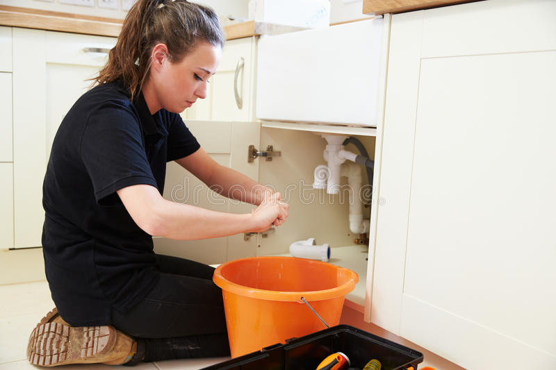 Female plumber preparing a pipe for a kitchen sink royalty free stock photos