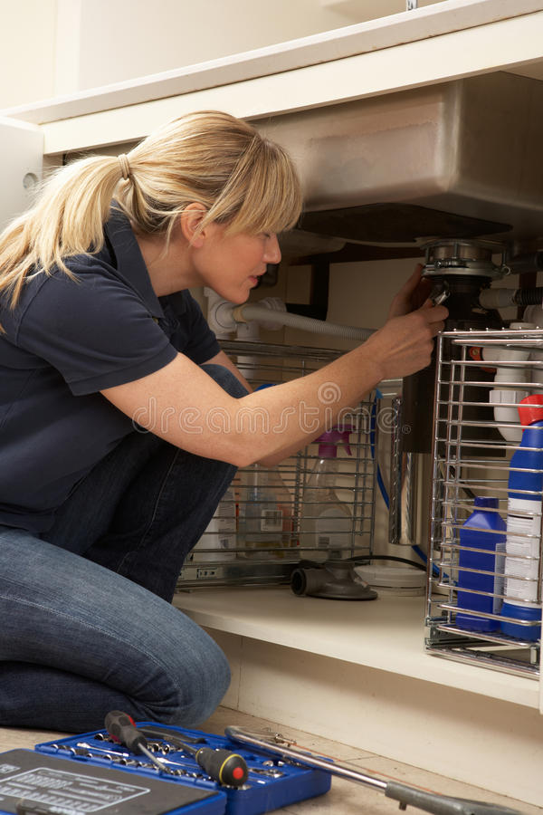 Female Plumber Working On Sink stock photo