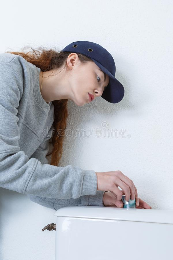 Female plumber working on toilet royalty free stock images