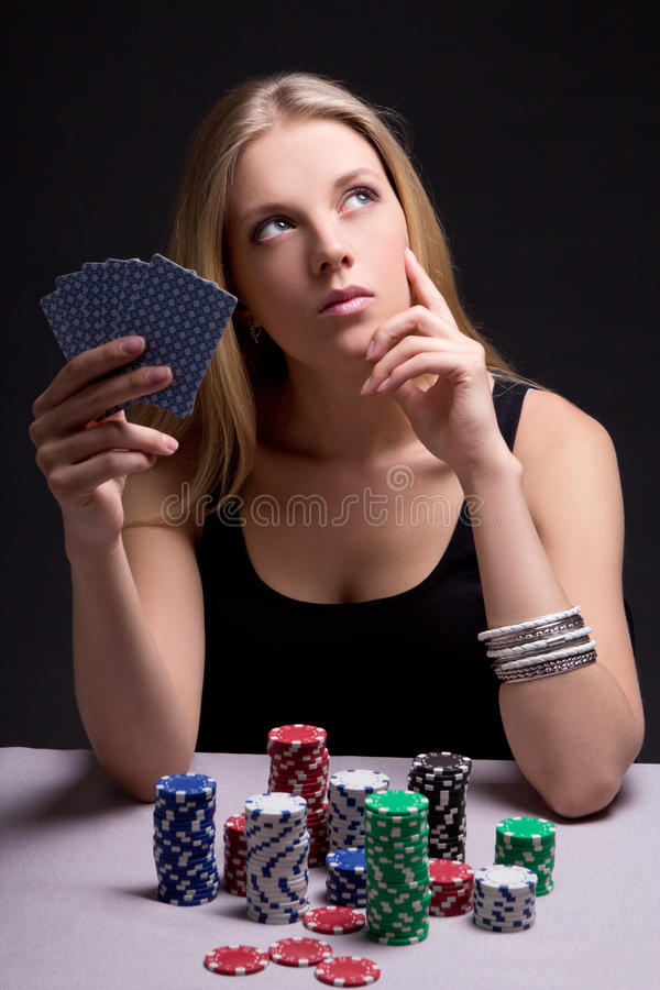 Female poker player in casino with cards and chips royalty free stock photography