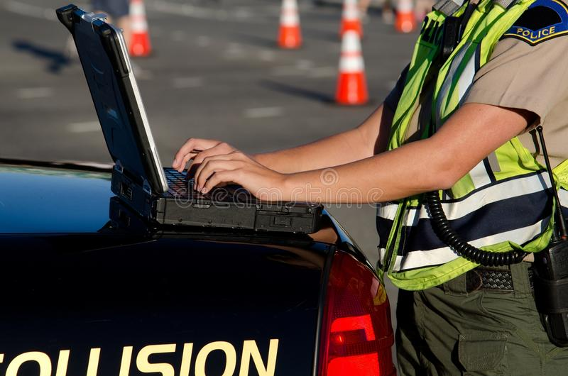 Female police officer. A female police officer types on her lap top computer while on a call royalty free stock photos