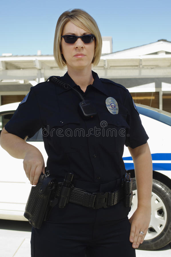 Female Police Officer. With gun standing by patrol car stock photography