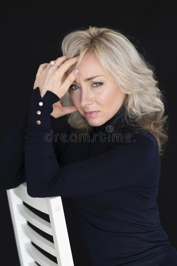 Female portrait on a black background. Woman the blonde, emotions. Black and White photon stock image