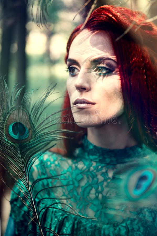 Female portrait with peacock feather on foreground. beauty makeup. stock photography