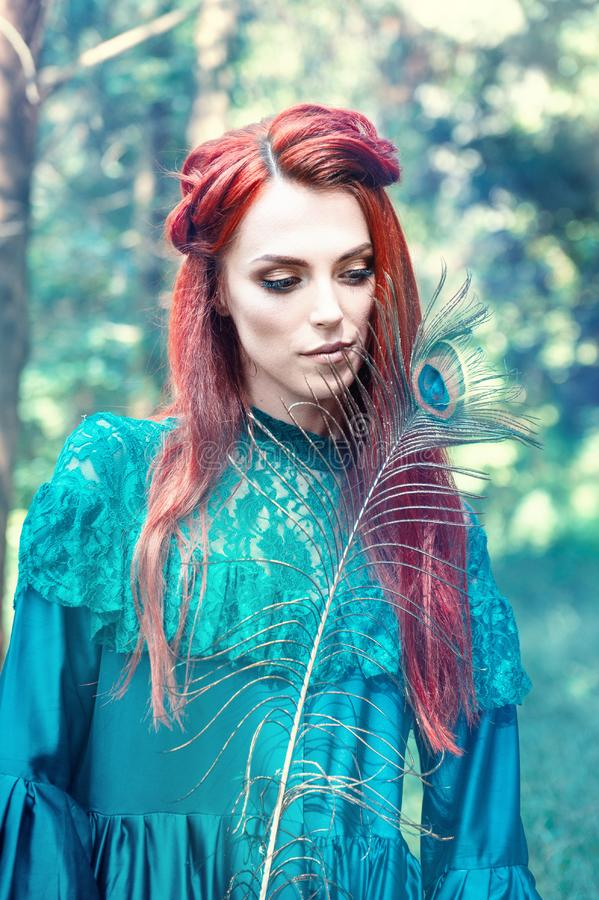 Female portrait with peacock feather on foreground. beauty makeup. royalty free stock photography