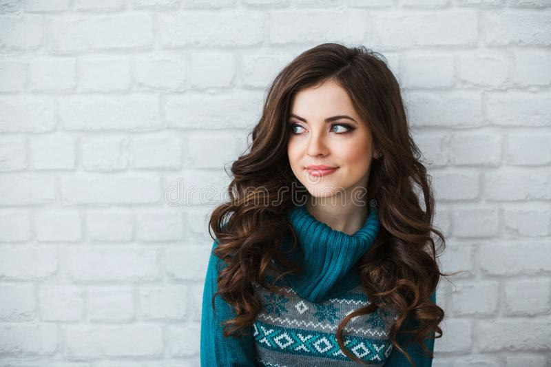 Female portrait. Young beautiful girl in a green sweater near a white brick wall. royalty free stock images