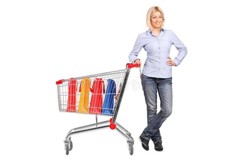 Female posing next to a shopping cart. Full length portrait of a smiling female posing next to a shopping cart full with shopping bags isolated on white royalty free stock photography