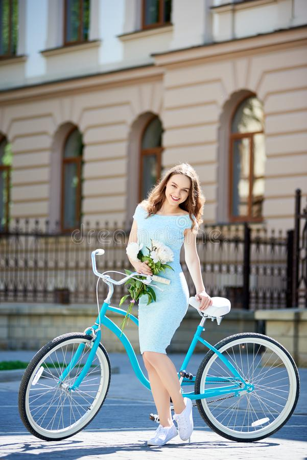Female posing with peonies near vintage bicycle looking at camera royalty free stock photography
