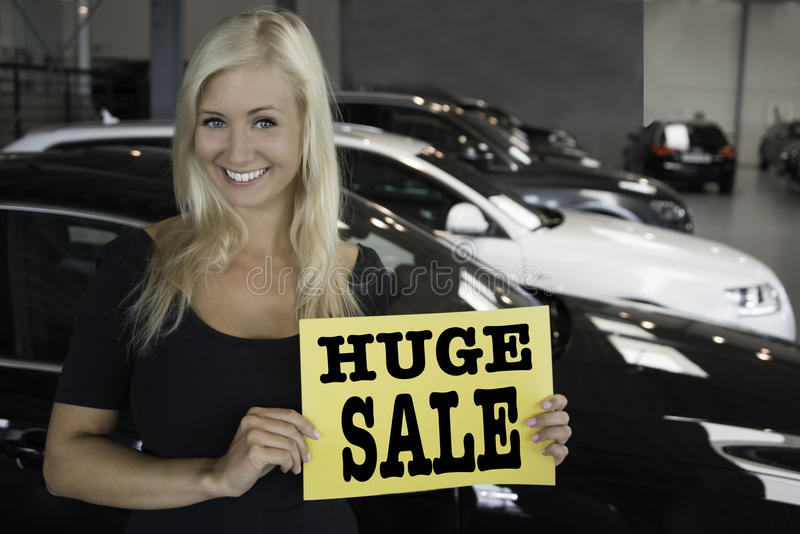 Download Female Posing With Sign In Front Of New Cars Stock Photo - Image: 31882976