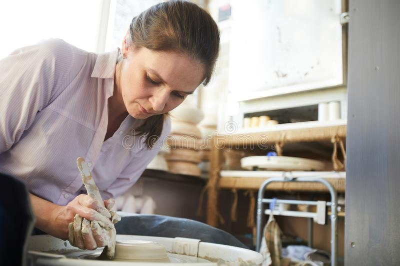 Female Potter using Wheel. Portrait of female potter creating handmade crockery using wheel in studio, copy space stock images