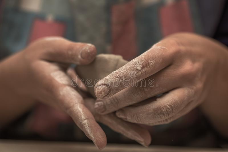 Female potter works with clay, craftsman hands close up with selective focus royalty free stock photography