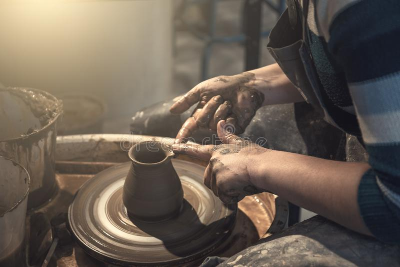 Female potter works with clay on pottery wheel, craftsman hands close up royalty free stock image