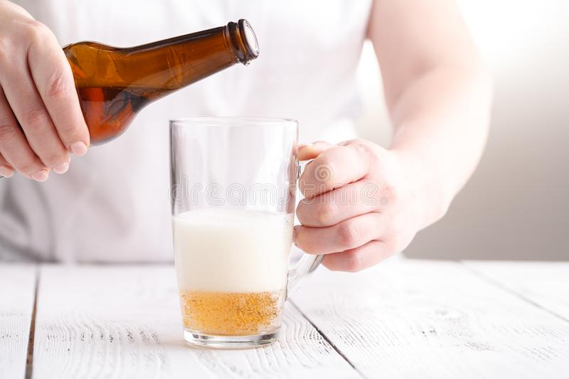 Female pouring beer in glass mug, relax concept stock photography