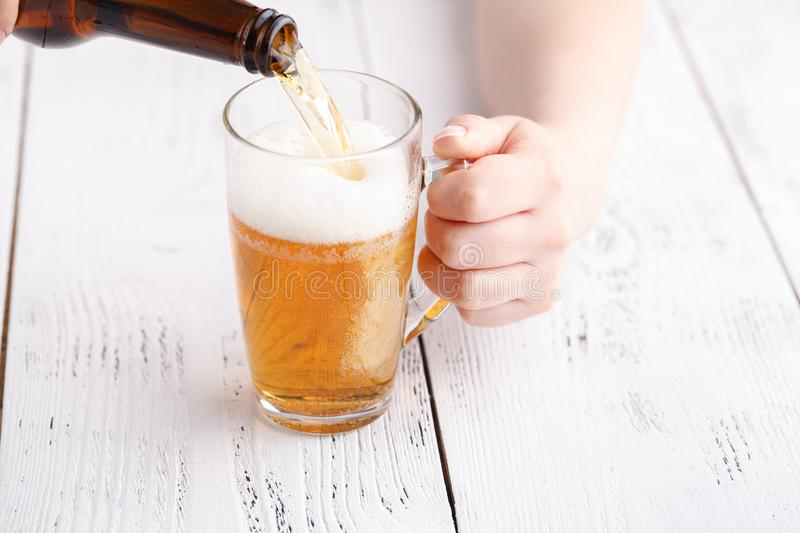 Female pouring beer in glass mug, relax concept stock image