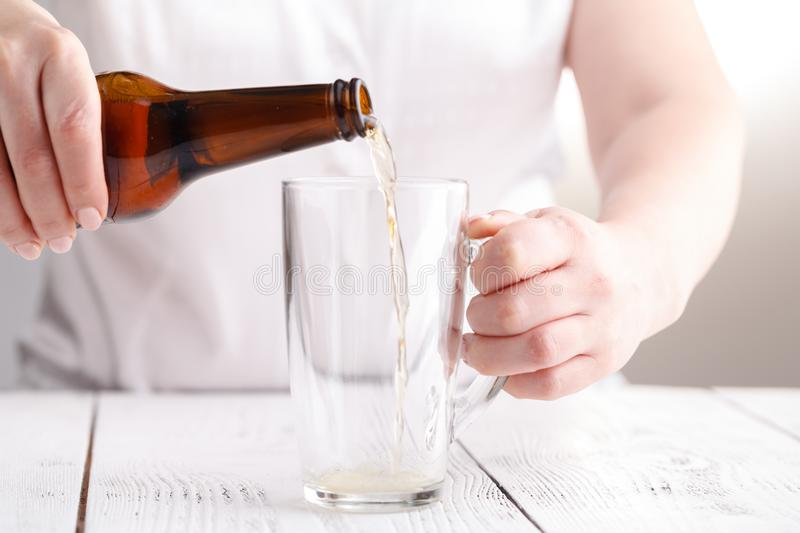 Female pouring beer in glass mug, relax concept royalty free stock photography