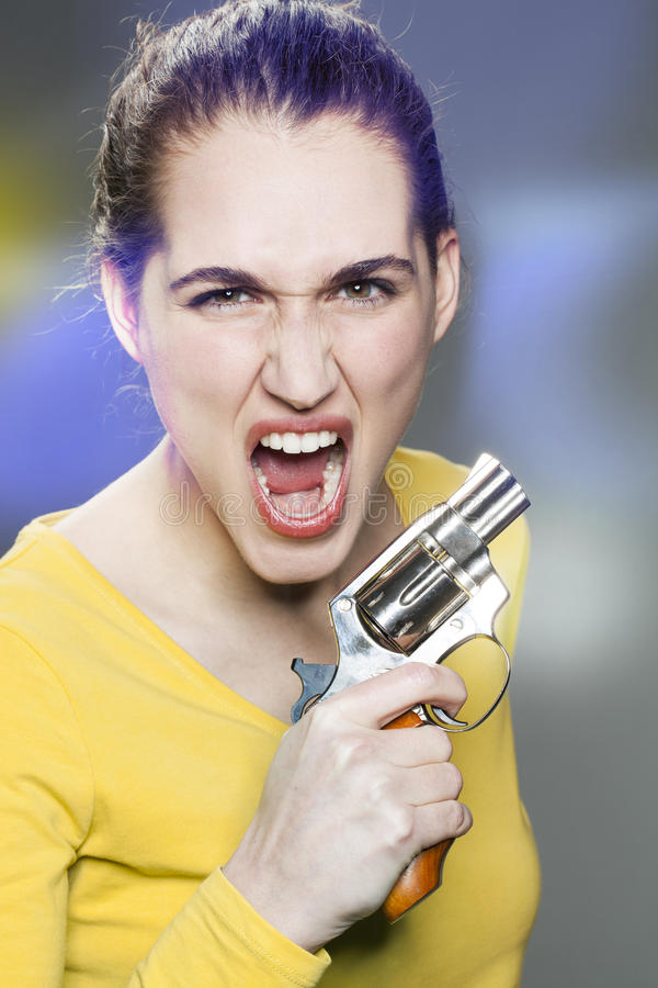 Female power concept for enraged young woman. Female power concept - enraged young woman shouting in holding a gun for revenge against aggression and violence stock images