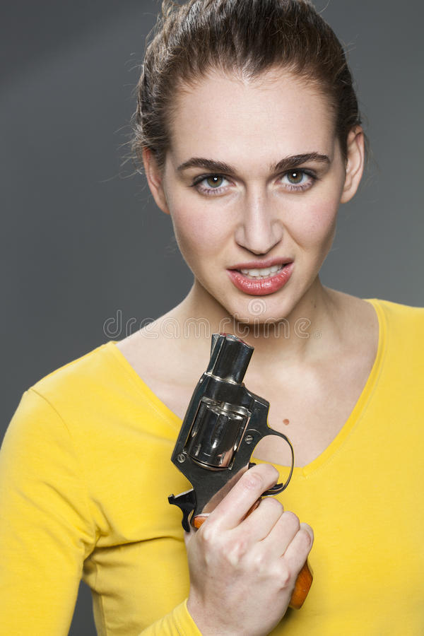 Female power concept for intimidating young woman. Female power concept - intimidating young woman with tied hair showing a handgun for impressing or expressing royalty free stock image
