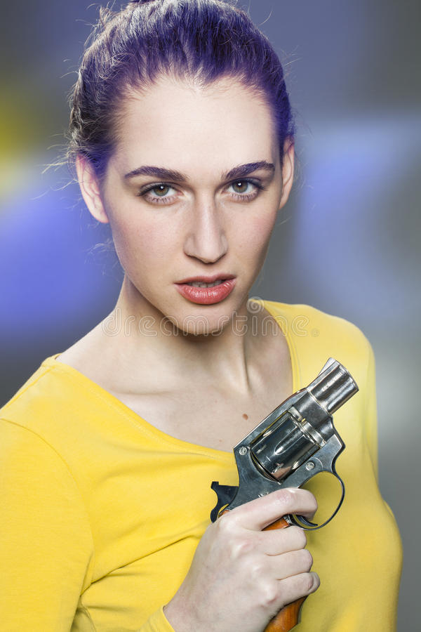 Female power concept,intimidating young woman. Female power concept - intimidating young woman with tied hair showing a handgun for impressing or expressing self stock photo