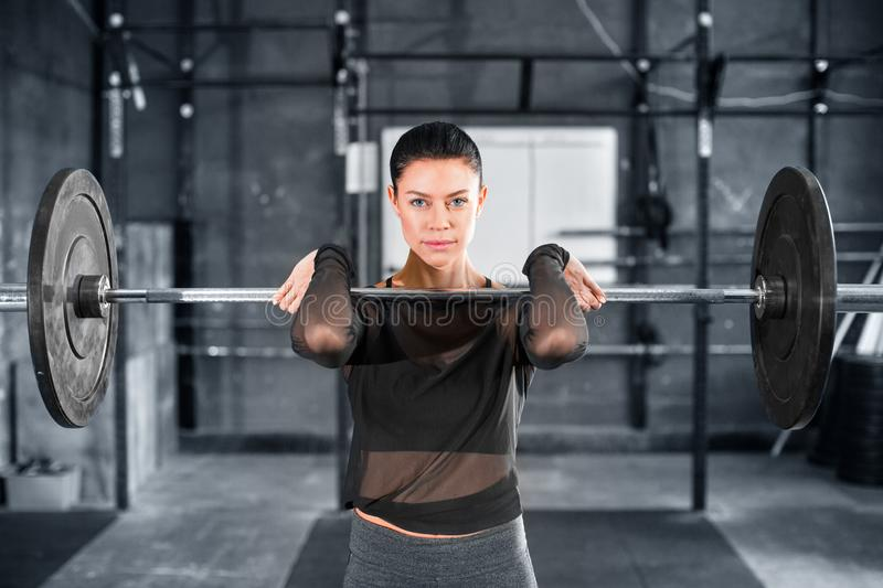 Female powerlifter doing a clean and jerk with heavy weights. Close up portrait royalty free stock photo