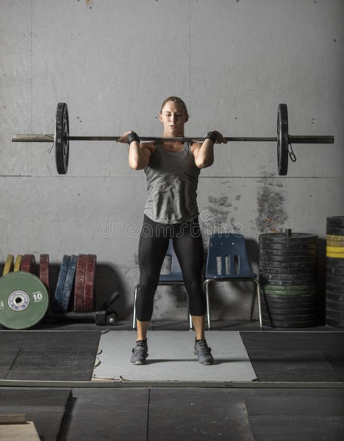 Female powerlifter doing a clean and jerk with heavy weights stock photos