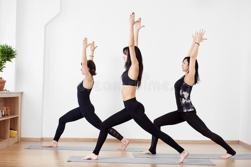 Female practicing yoga asana with hands up, turning in one direction. Group of people in Warrior pose at gym. Side view royalty free stock image
