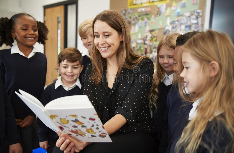 Female primary school teacher reading to a class of school kids standing around her in the classroom. Close up stock photos