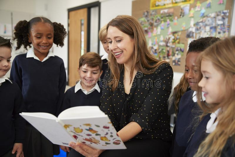 Female primary school teacher reading to a class of school kids standing around her in the classroom. Close up stock photo