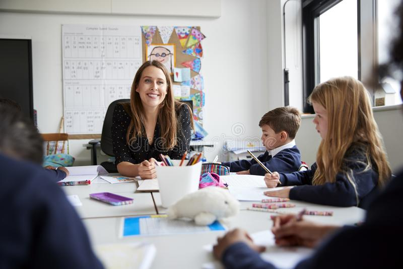 Female primary school teacher sitting at a table smiling to camera during a lesson with a group of schoolchildren, low angle, sele. Ctive focus royalty free stock photos