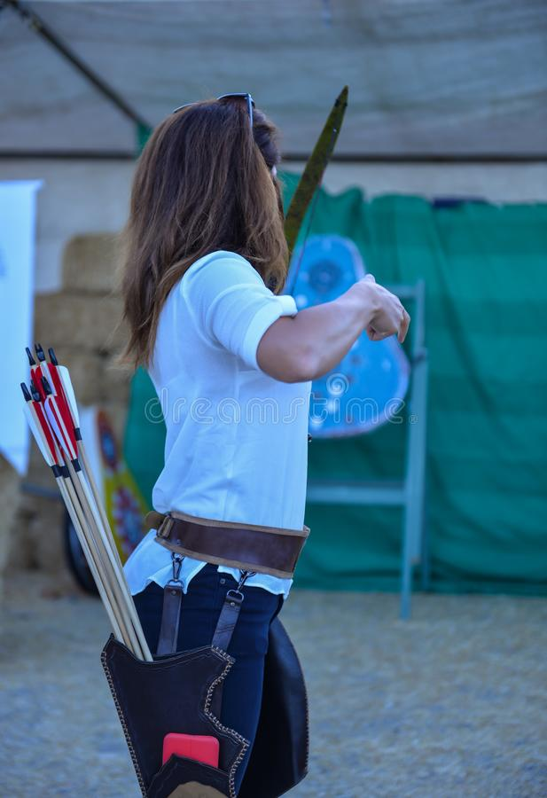 Archery trainings, shots and traditional local outfits. Female professional archer shooting position royalty free stock image