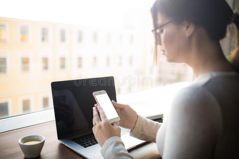 Woman using cellphone. Female professional blog writer holding mobile phone with white empty copy space screen background for advertising text message during stock images