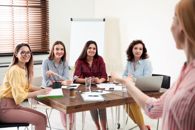 Female professional  trainer working with ladies in office. Women power concept stock photo