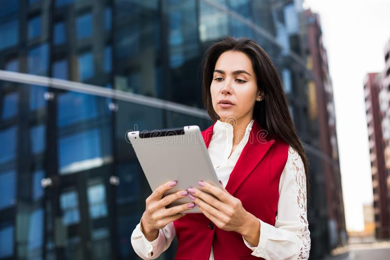 Female entrepreneur using digital tablet for char, standing near business centre during break at job royalty free stock photos