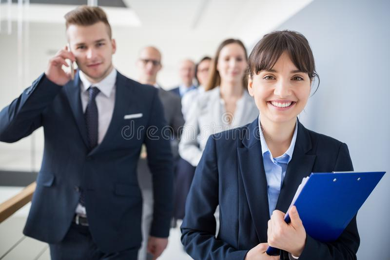 Female Professional Holding Clipboard While Walking With Team royalty free stock photography