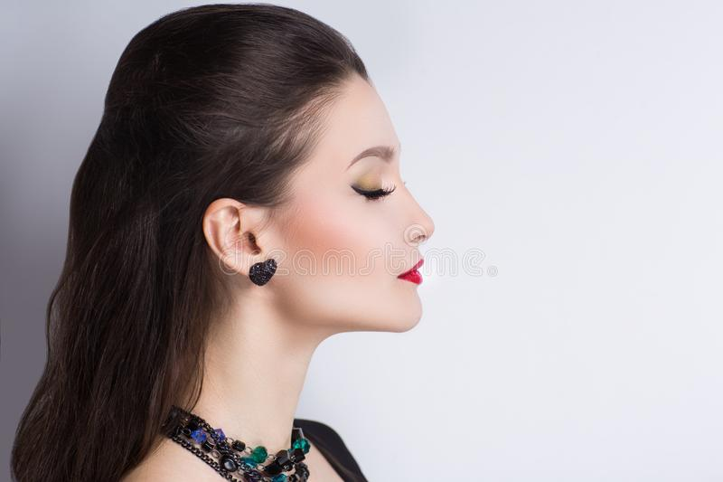 Female profile perfect. Closeup portrait beautiful girl woman lady with volume combed hair styling hair-do. Luxury long black hair. Bright make up, red lip-gloss royalty free stock photo