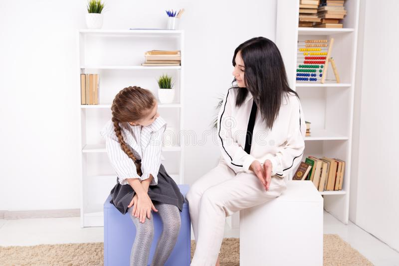 Female psychologist counseling little girl in the cabinet. Female psychologist counseling little girl in the cabinet stock photography