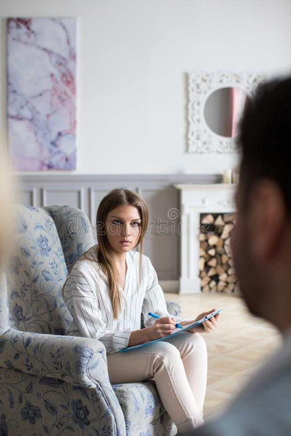 Female psychologist having therapeutic session with young couple on a sofa in office stock image