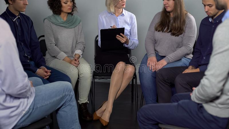 Female psychotherapist listening and supporting depressed woman, group therapy stock image