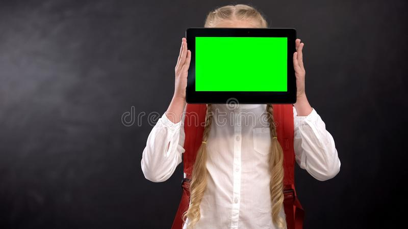 Female pupil closing face with green screen tablet, modern educational system. Stock photo royalty free stock images