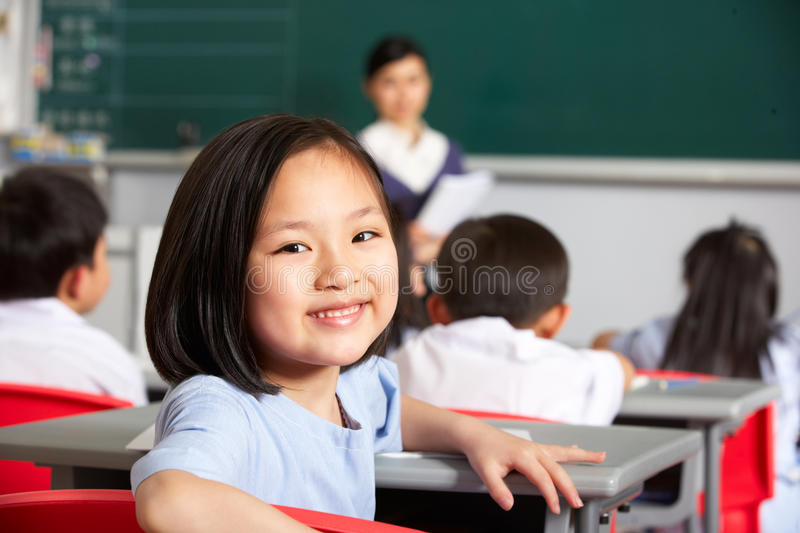 Female Pupil Working At Desk In Chinese School