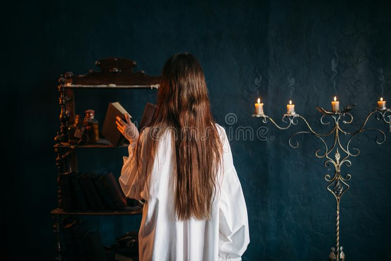 Female puts old spellbook on shelf, back view. Female person in white shirt puts old spellbook on shelf, back view, candles on background. Dark magic, occultism stock photo
