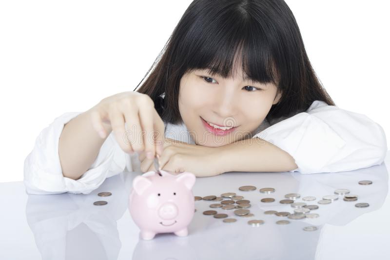 Female depositing American coins piggy bank isolated, white background royalty free stock photos