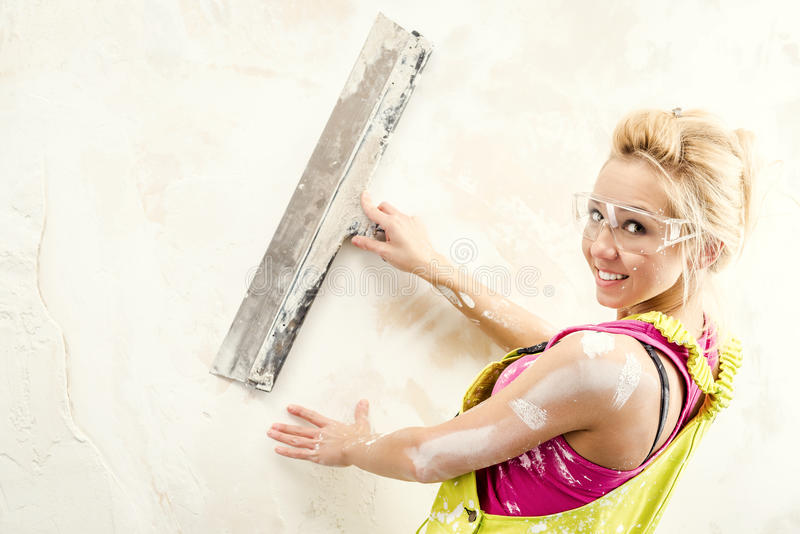 Female with putty knife working stock photo