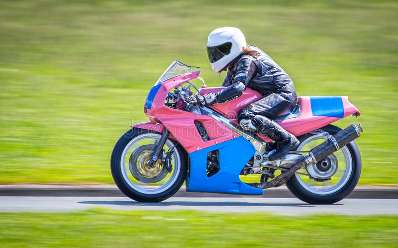 Female racer on motorbike royalty free stock image