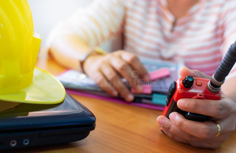 Female radio operator using Walkie - Talkie to communicate with other people and working with document. On working desk, Communication concept stock image