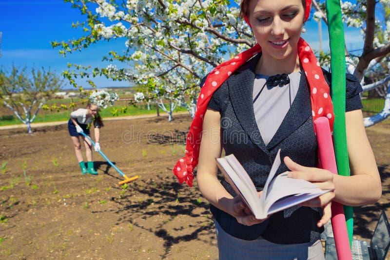 Female raking soil on garden royalty free stock photos