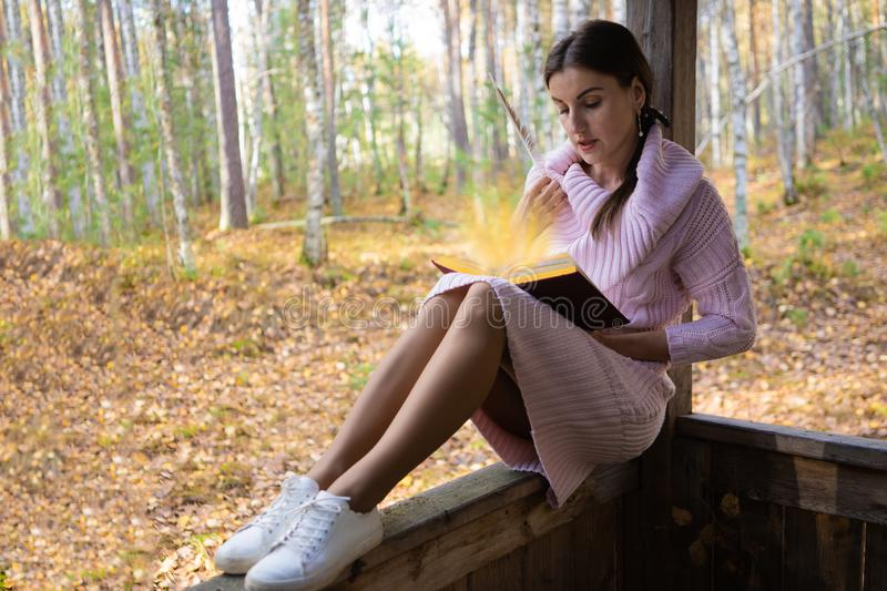 Female reads a magic book in a forest in the past. Magical light shines from the book. stock images