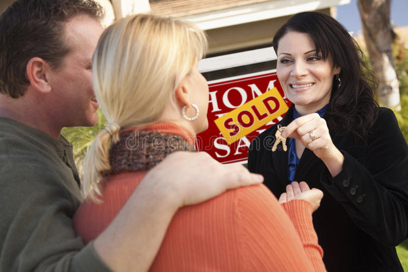 Female Real Estate Agent with Happy Couple, House. Attractive Hispanic Female Real Estate Agent Handing Over New House Keys to Happy Couple royalty free stock photo