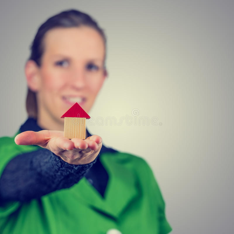 Female real estate agent holding out a model house. Retro vintage or instagram style image of a smiling young real estate agent holding out a model house on the royalty free stock image