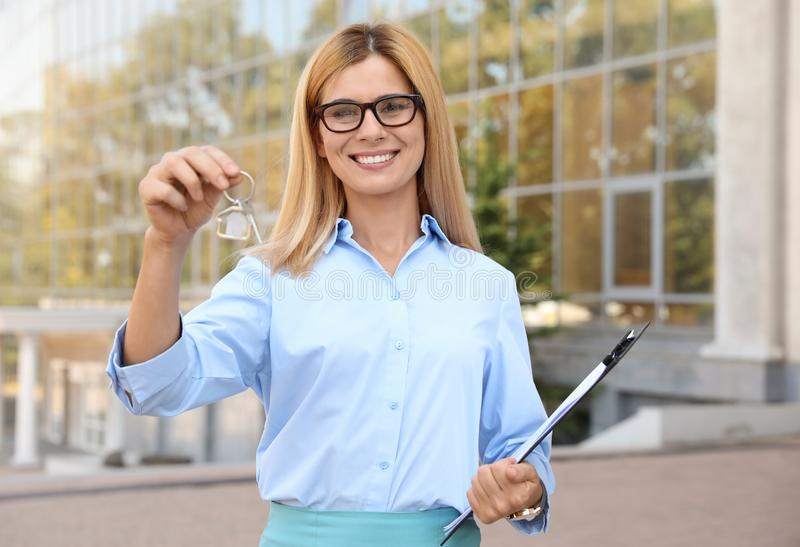 Female real estate agent with house key royalty free stock image